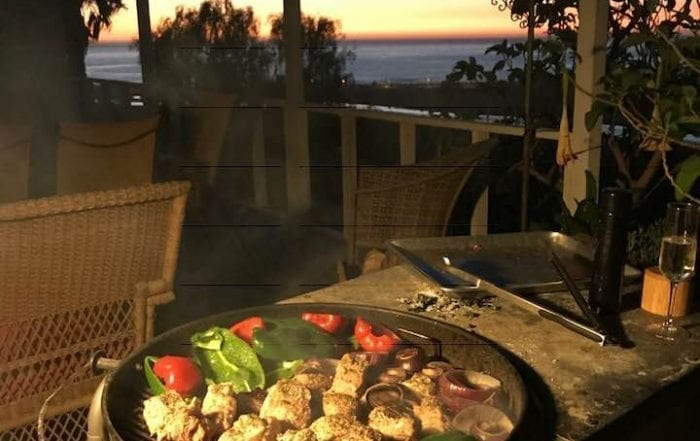 Vegetables grilling iwth a view of a sunset over the ocean
